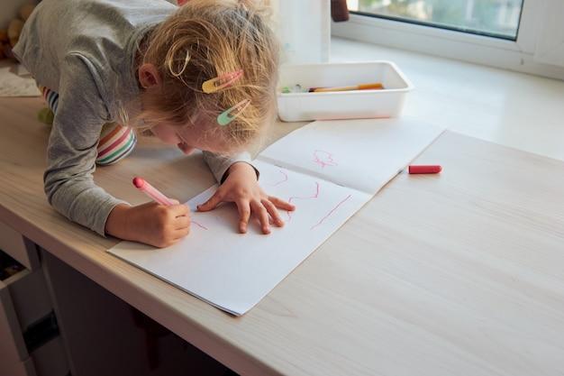 3세 소녀가 그림을 그립니다. 집에 있는 어린이, 유치원 및 유치원은 covid-19 동안 문을 닫습니다.