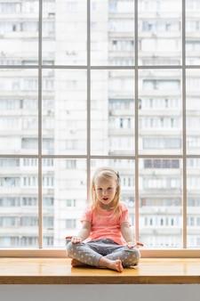 ロータスに座っている3歳の女の子は、背景に都市の建物と窓の前に組んだ足でアーサナをポーズします。