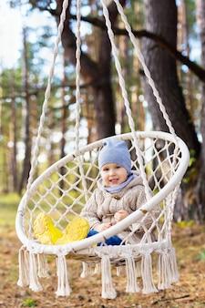 3-летний ребенок качается в подвесном кресле на открытом воздухе
