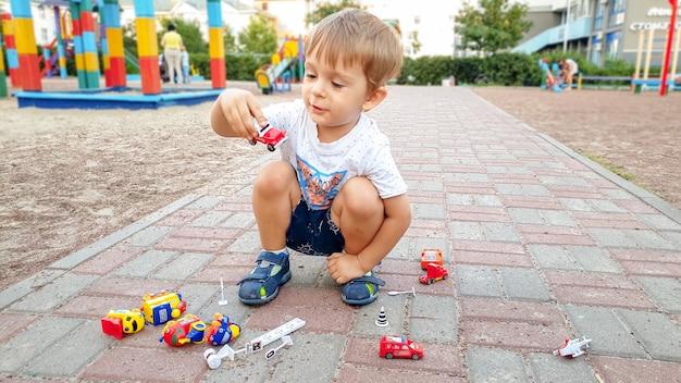 Tシャツとショートパンツを着た3歳の男の子が遊び場で地面に座り、たくさんのカラフルなおもちゃで遊んでいる