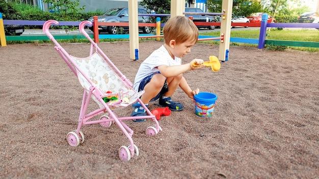 公園の遊び場で遊ぶ人形用のおもちゃの乳母車を持った 3 歳の男の子