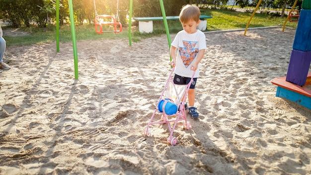 遊び場で人形用の乳母車で遊ぶ 3 歳の幼児の男の子