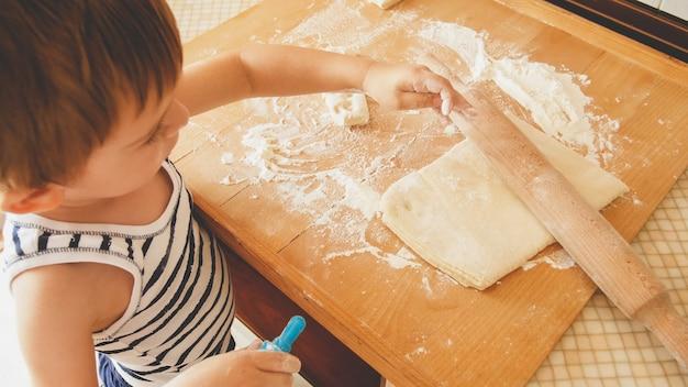 3 세 유아 소년 나무 보드에 반죽을 굴리고 아침에 쿠키를 굽고