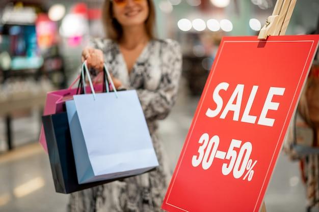 Красная подставка распродажа со скидками 30 и 40 процентов, на фоне которой стоит счастливая молодая модель в солнечных очках с цветными сумками