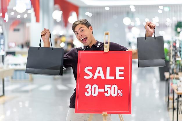 Молодой парень ставит против баннера распродажи и скидки до 30-50 процентов, держа в обеих руках две черные сумки с широкой улыбкой. эмоция радости. черная пятница. день больших скидок.
