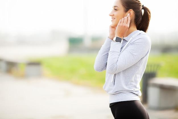 緑豊かな公園で休んでいる間、スポーツウェアでうれしそうなフィットネス女性30代のbluetoothイヤーポッドに触れて携帯電話を保持している写真