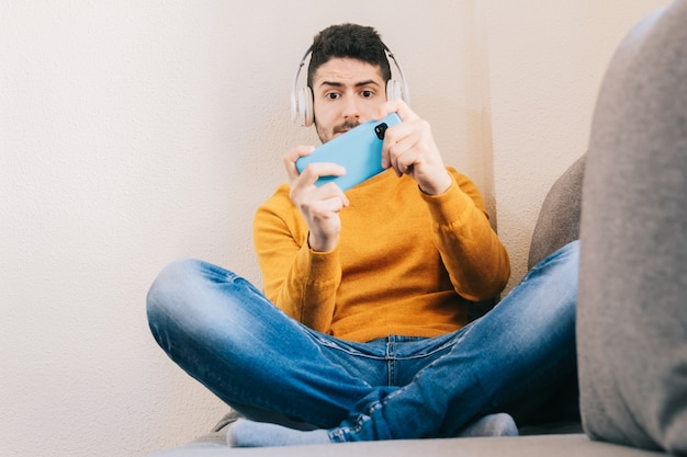 헤드폰을 끼고 집에 있는 소파에 앉아 흥분한 표정으로 휴대폰으로 가상 현실 게임을 하고 있는 30세 남성.