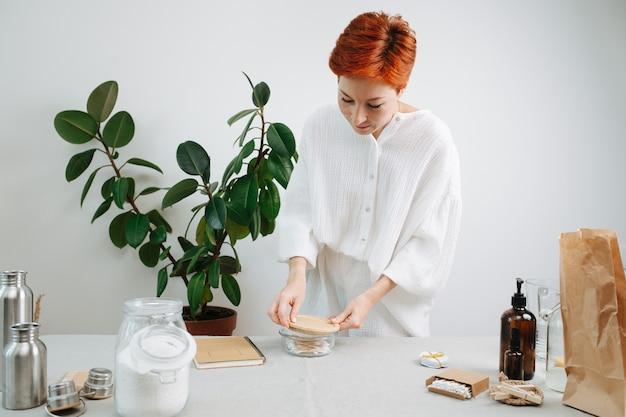 30-летняя женщина снимает деревянную крышку со стеклянной тары с экологически чистыми ватными палочками.
