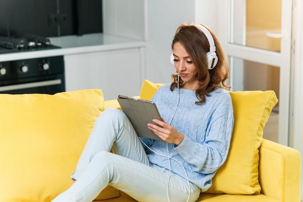 白いイヤホンを着たウェーブのかかった茶色の髪を持つ熱狂的な30歳の少女は、音楽を聴き、ラップトップまたはタブレットを使用して、居心地の良い家の黄色のソファで休んでいます。
