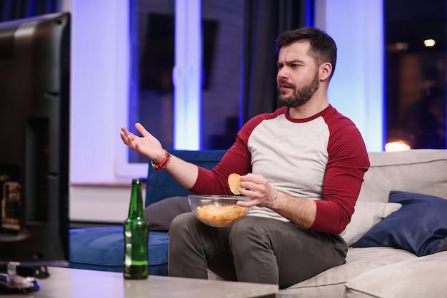 Симпатичный современный позитивный 30-летний парень с ухоженной бородой наслаждается жареным картофелем во время эмоционального просмотра игры любимой футбольной команды на телевидении дома