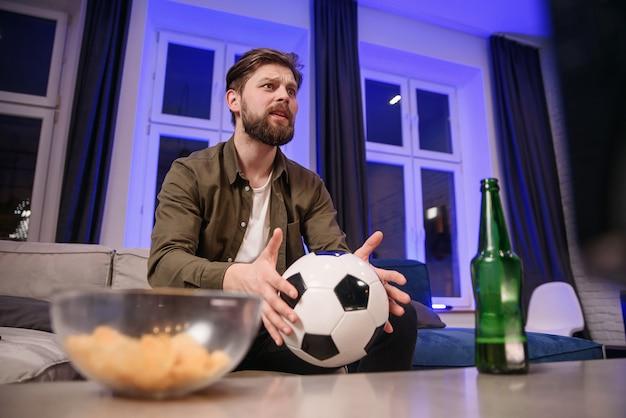 Взволнованный симпатичный 30-летний бородатый парень с футбольным мячом в руке недоволен неудачной игрой своей любимой команды и падает на кушетку