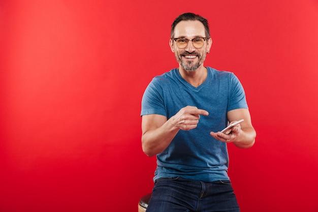 Довольный улыбающийся мужчина 30-х годов, набрав текст сообщения или прокрутки в социальной сети с помощью смартфона, изолированных на красном фоне