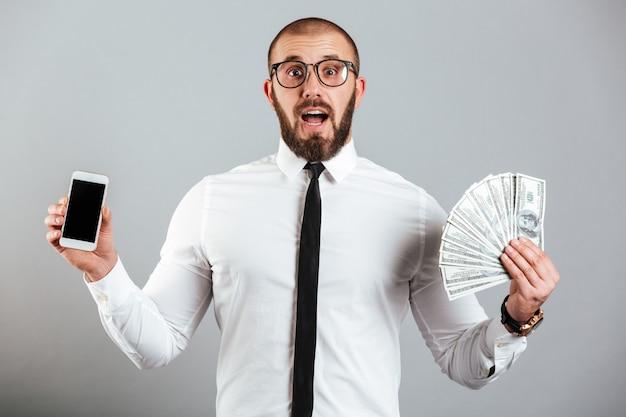Фотография возбужденного парня 30-х годов в очках и костюме, держащего сотовый телефон и веер денег долларов, изолированных на серую стену