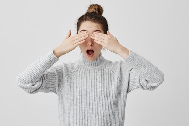 口を開けて立っている手で目を覆っているブルネットの女性30代。ニュースに襲われた若い女性は現実を見たくない。感情の概念