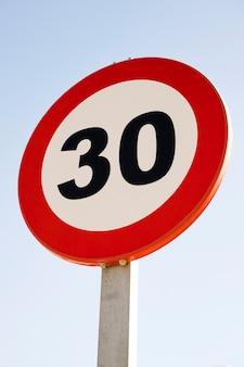 Круглый знак ограничения скорости 30 против голубого неба