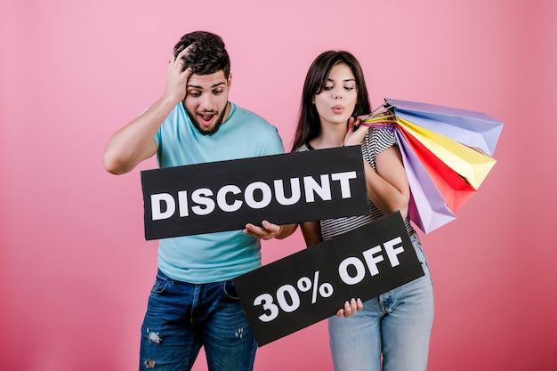 幸せな笑みを浮かべてハンサムなカップルの男性と女性のサインとカラフルなショッピングバッグ30%割引