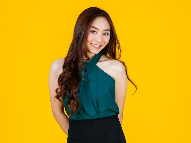 30代のキュートでチャーミングな巻き毛のアジアの女性ブルネットは、広告の使用目的のために楽しく前向きなジェスチャーでカメラにポーズをとります。黄色の背景に分離されたスタジオフラッシュで撮影。