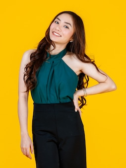 30대 귀엽고 매력적인 곱슬머리 아시아 여성 브루네트는 광고 목적으로 즐겁고 긍정적인 몸짓으로 카메라를 향해 포즈를 취합니다. 노란색 배경에 격리된 스튜디오 플래시로 촬영했습니다.