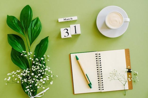 Деревянный кубик календарь 31 марта. блокнот, чашка кофе, букет цветов на зеленом фоне. concept hello spring вид сверху плоская планировка макет
