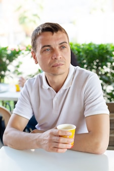 A 35-40 year old man is a lonely sad man sitting with a glass of coffee in a street cafe.