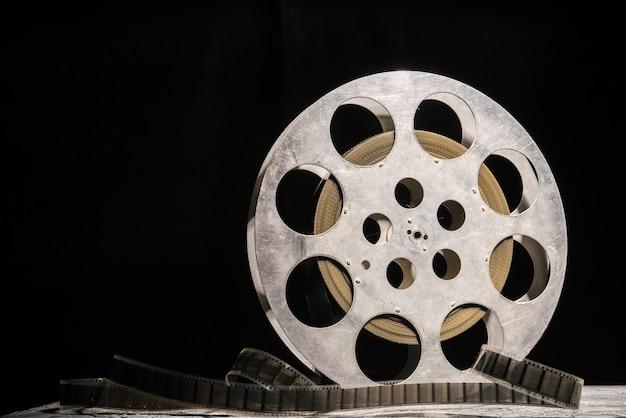 暗い背景に劇的な照明を備えた35mmフィルムリール-画像