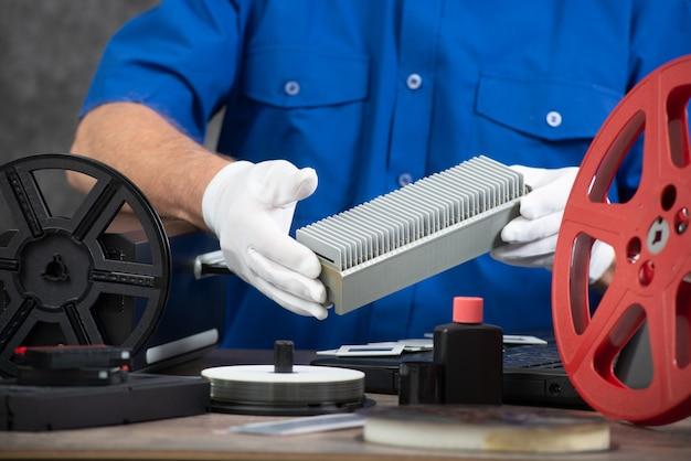 古い35 mmフィルムスライドをデジタル化する白い手袋を持つ技術者