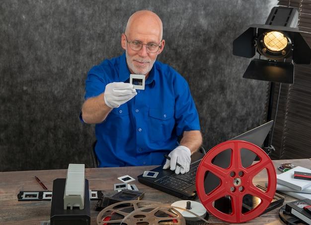 Техник с белыми перчатками оцифровывает старую пленку 35 мм