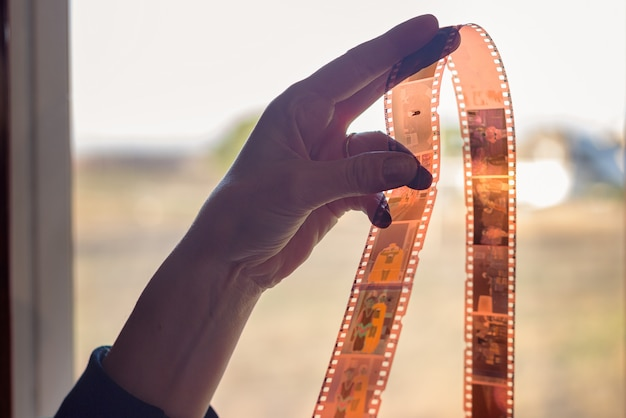 35mmの長さのフィルムストリップを持っている女性の手