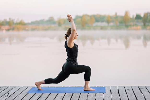 A 36-year-old young caucasian woman practices yoga outdoors near a river on a wooden pier in the morning