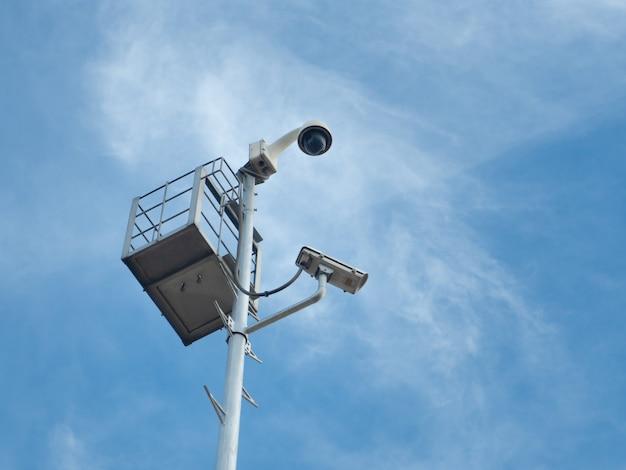 Купольная камера видеонаблюдения и камеры видеонаблюдения на 360 градусов установлены на колонне против голубого неба.