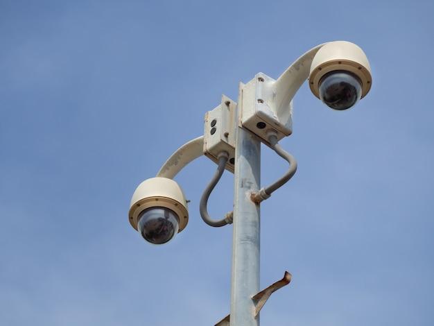 Купольная система видеонаблюдения с углом обзора 360 градусов установлена на колонне против голубого неба.