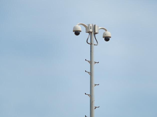 Купольная система видеонаблюдения на 360 градусов установлена на колонне против голубого неба.