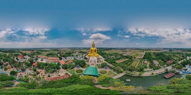 タイ、アントン県、ワットムアン寺院にある大きな古代の黄金の仏像の360度のパノラマ空撮、ドローンの高角度の上面図