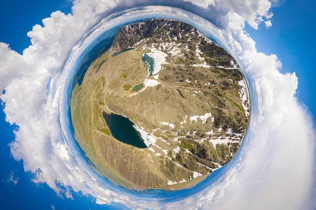 澄んだ青い湖の下にある、雪のないコアを持つ山のパノラマ。パノラマの街360ショット