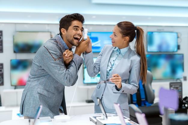 Пара, одетая в деловую одежду, пробует камеру на 360 градусов, стоя в техническом магазине