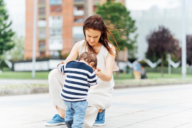 37歳の母親と1人の赤ちゃんが路上で歩くように教えている