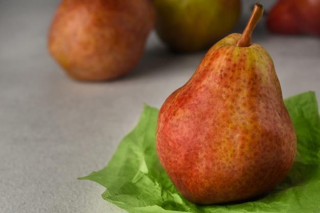 明るい背景に赤い熟した梨。しわくちゃの緑の包装紙と背景に3つの梨の梨。