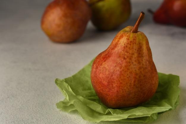 明るい背景に赤い熟した梨。しわくちゃの緑の包装紙と背景に3つの梨の梨。フルーツの背景。