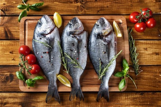 茶色の素朴な表面に3つの生のドラド魚のトップビュー