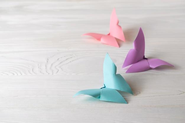 テキストのコピースペースを持つ3つのカラフルな折り紙蝶と白い木製の表面