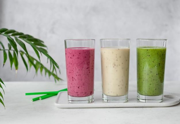 3 стакана смузи на серой стене с зелеными листьями. пюре из ежевики, банана, киви и шпината