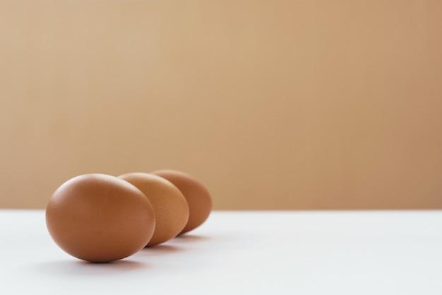 3つの未塗装卵が白いテーブルの上にあります。イースターのコンセプトです。環境にやさしいコンセプト