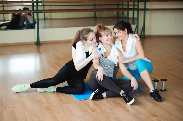 3人の陽気なスポーツウーマンがジムでエクササイズした後、笑って楽しんでいます。かわいい女性はハードな身体活動の後に休憩を取る