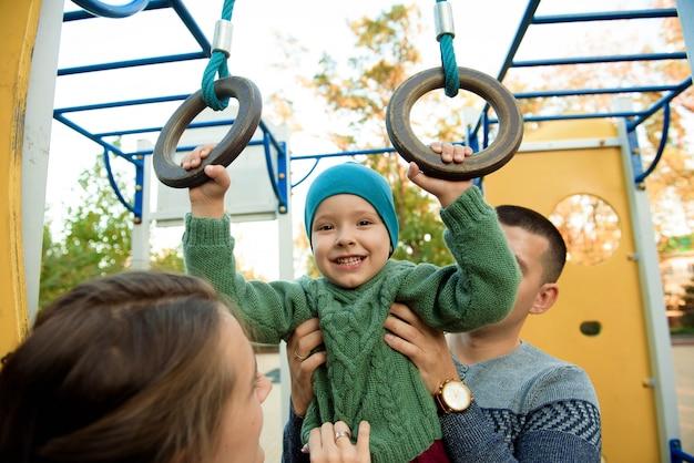 かわいい3歳の少年は興奮して黄色の遊び場スライドで遊ぶ。