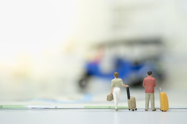 Бизнесмен и женщина с багажом, стоя на карте и глядя на 3 колеса автомобиля.