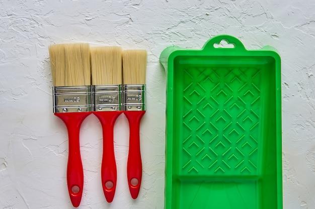 3 щетки с красными ручками и зеленым подносом краски на белом бетоне. инструменты и аксессуары для ремонта дома. вид сверху