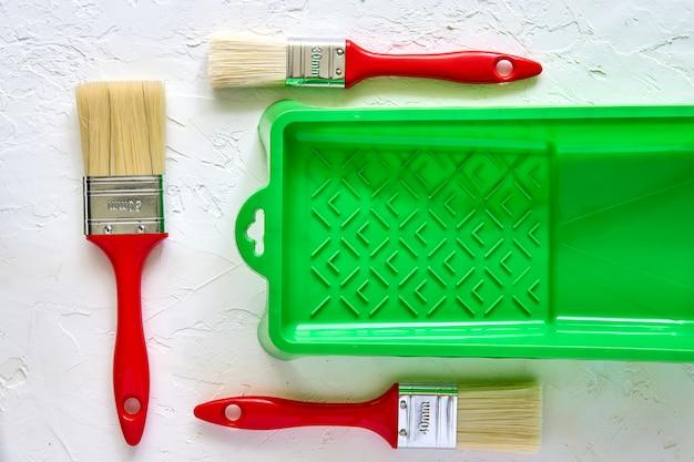 3 щетки с красными ручками и зеленым подносом краски на белой конкретной предпосылке. инструменты и аксессуары для ремонта дома. вид сверху