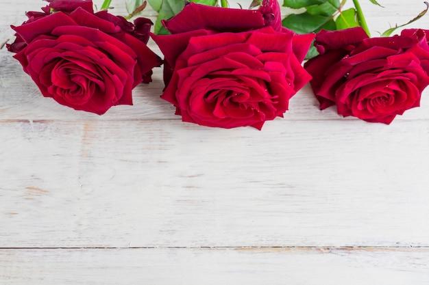 コピースペースを持つ白い木製の背景に3つの新鮮な咲くバラ