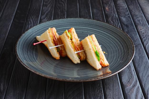 レセプションの前菜。皿の上の3つのミニクラブサンドイッチ