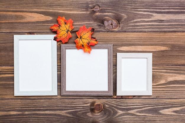 茶色の木製テーブルとオレンジ色のカエデの葉の3つの空のフォトフレーム。コピースペース